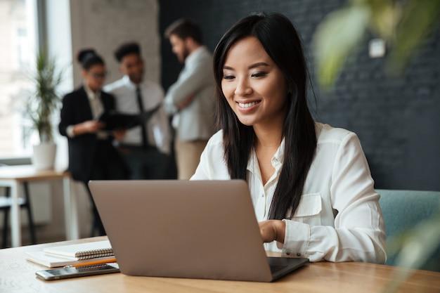 Alegre empresária asiática jovem usando laptop Foto gratuita