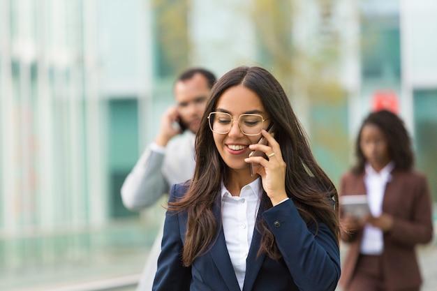 Alegre empresária latina com telefone descendo rua da cidade Foto gratuita