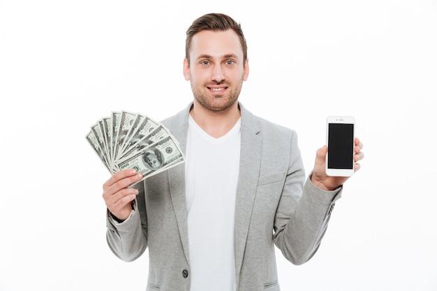 Alegre empresário feliz segurando o dinheiro e mostrando a exibição do telefone. Foto gratuita