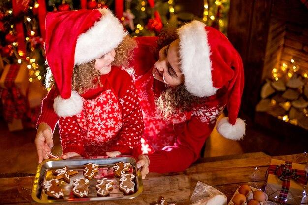 Alegre encaracolada menina bonitinha e sua irmã mais velha em gorros cozinhar biscoitos de natal Foto Premium
