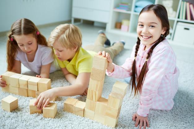 Alegre estudante se divertindo com cubos de madeira Foto gratuita