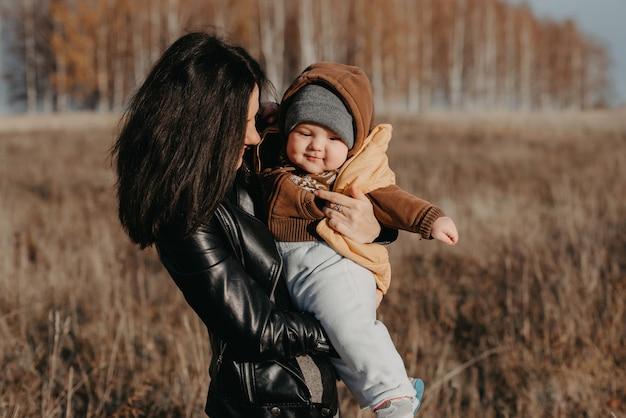 Alegre, feliz, jovem, mãe, com, dela, menino bebê menino, filho, em, dela, mãos, em, a, outono Foto Premium