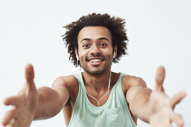 Alegre homem africano em fones de ouvido com fio sorrindo esticando as mãos tentando roubar seu telefone celular. Foto gratuita