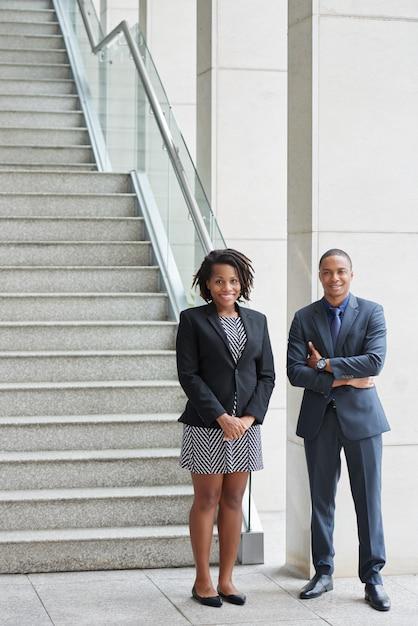 Alegre homem afro-americano e mulher em pé no escritório na parte inferior da escada Foto gratuita