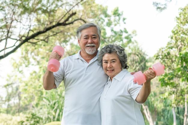 Alegre homem idoso e mulher sênior com halteres para treino no parque, eles sorrindo com bom e saudável juntos Foto Premium