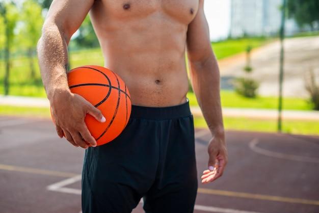 Alegre homem segurando uma bola de basquete Foto gratuita