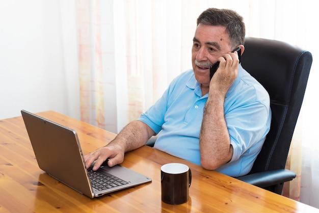 Alegre homem sênior trabalhando no laptop enquanto fala ao telefone Foto Premium