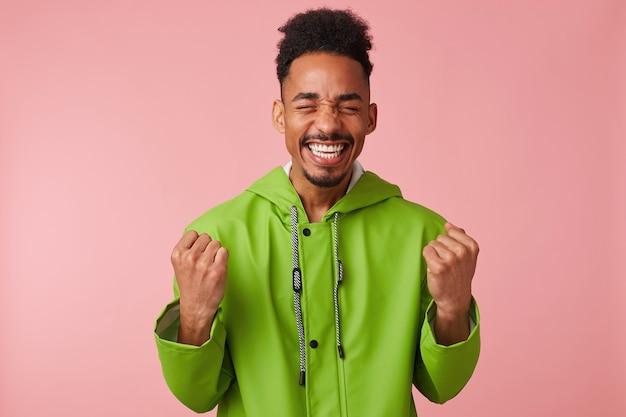 Alegre jovem afro-americano bonito se levanta, cerrou os punhos, amplamente sorrindo e absolutamente feliz - ele ganhou na loteria! Foto gratuita