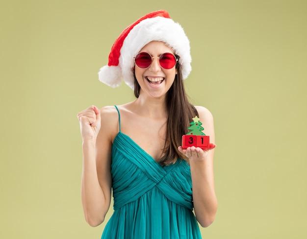 Alegre jovem caucasiana com óculos de sol e chapéu de papai noel segurando o punho e segurando o enfeite de árvore de natal Foto gratuita