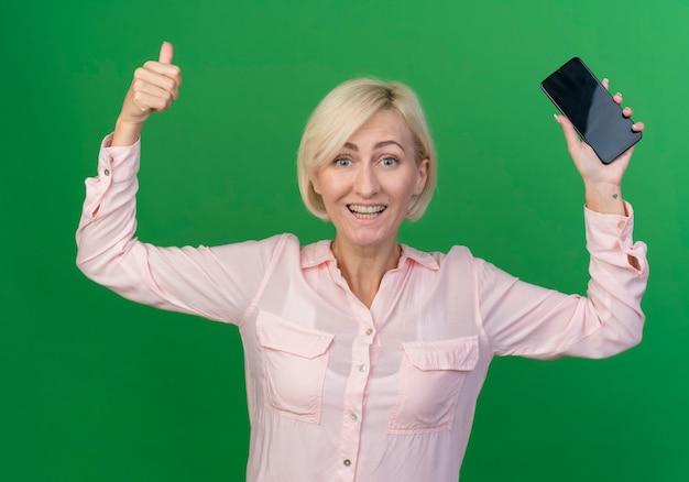 Alegre jovem loira levantando o celular e mostrando o polegar Foto gratuita