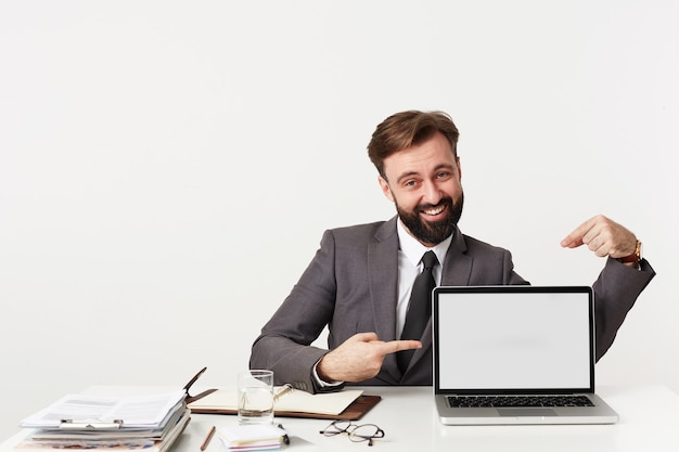 Alegre jovem morena com roupas formais, sentado à mesa de trabalho com um laptop moderno e apontando na tela com os indicadores, olhando alegremente para a frente com um largo sorriso Foto gratuita