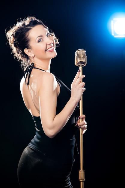 Alegre, jovem, mulher, cantor, segurando, dourado, vintage, microfone, iluminado, projetor Foto gratuita