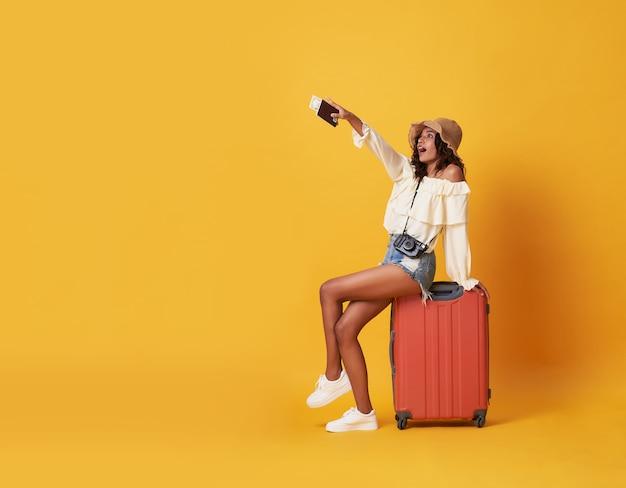 Alegre jovem negra vestida com roupas de verão, sentado em uma mala e apontando o dedo no espaço da cópia Foto Premium