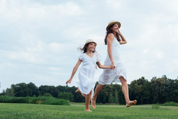 Alegre mãe e filha caminhando na natureza Foto gratuita