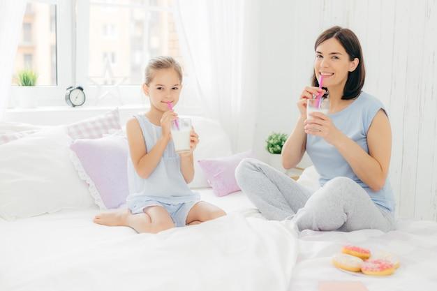 Alegre mãe e filha vestida de pijama, tomar café da manhã Foto Premium
