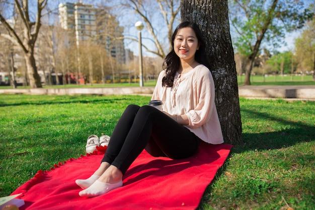 Alegre menina asiática positiva, aproveitando o fim de semana ao ar livre Foto gratuita