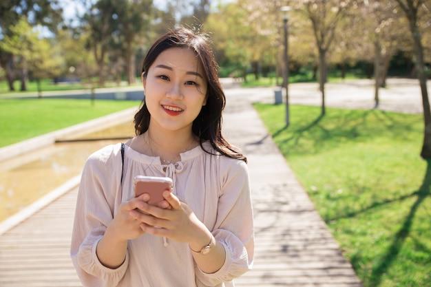 Alegre menina positiva com celular posando ao ar livre Foto gratuita