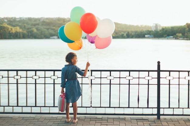 Alegre menina segurando balões coloridos e mala infantil Foto gratuita