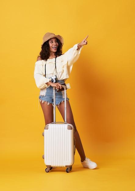 Alegre mulher africana jovem vestida com roupas de verão em pé com uma mala Foto Premium