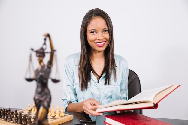 Alegre mulher afro-americana com livro na mesa com smartphone, estátua e xadrez Foto gratuita