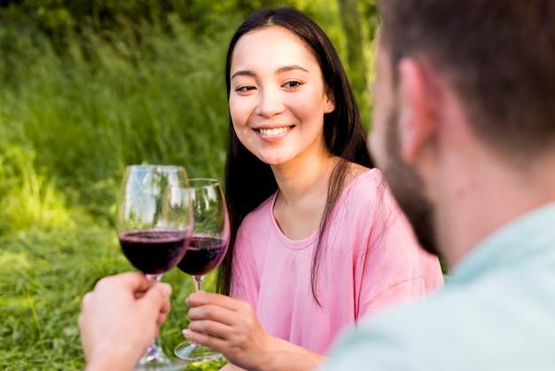 Alegre mulher asiática brindando o copo de vinho com namorado e sorrindo Foto gratuita