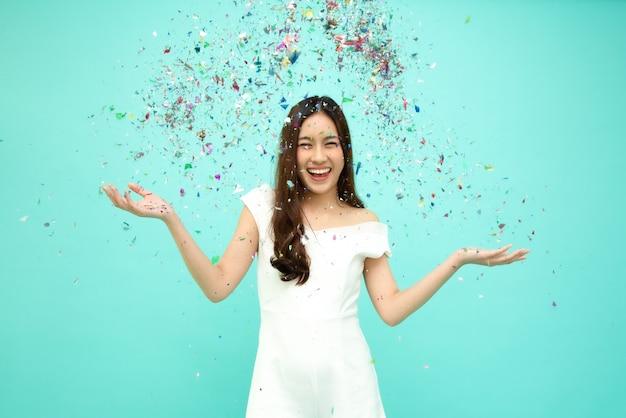Alegre mulher asiática jovem comemorando com confetes coloridos Foto Premium