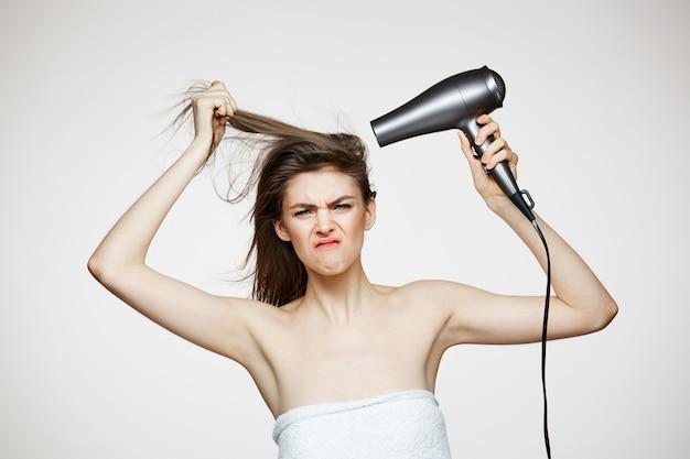 Alegre mulher bonita toalha sorrindo rindo cantando com secador de cabelo fazendo careta. spa de beleza e cosmetologia. Foto gratuita