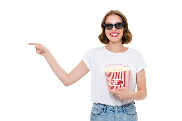 Alegre mulher caucasiana segurando pipoca assistir filme e apontando. Foto gratuita
