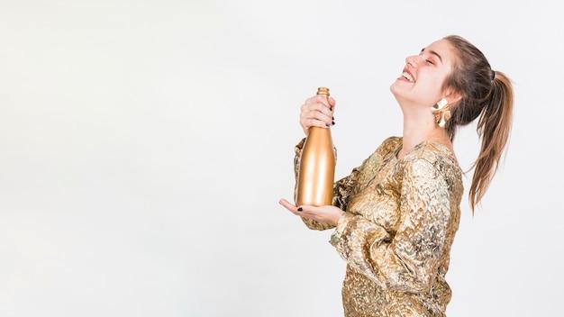 Alegre mulher em pé com uma garrafa de champanhe Foto gratuita