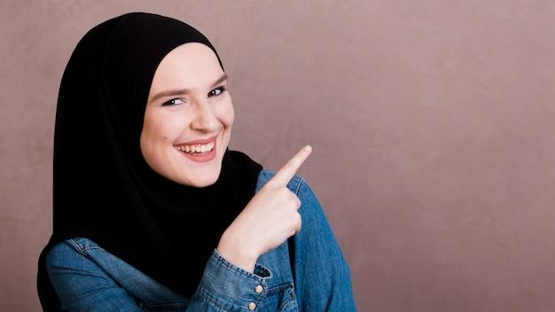 Alegre mulher islâmica apontando o dedo para algo Foto gratuita