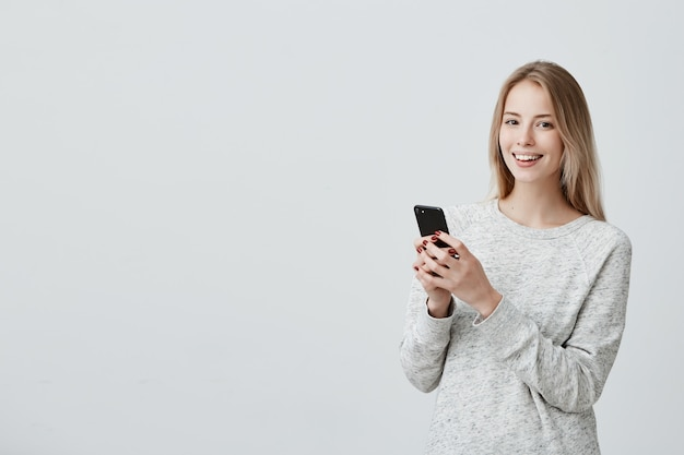 Alegre mulher loira jovem com sorriso fofo posando dentro de casa, usando telefone celular, verificando o feed de notícias em suas contas de rede social. mulher bonita, navegar na internet no celular Foto gratuita