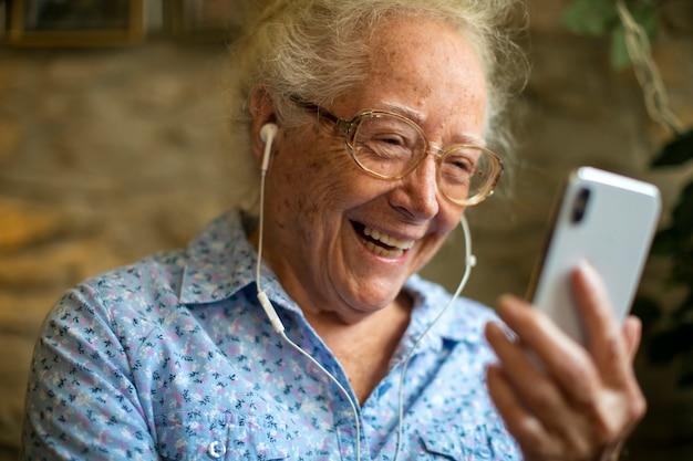 Alegre mulher sênior fazendo uma chamada de vídeo Foto Premium