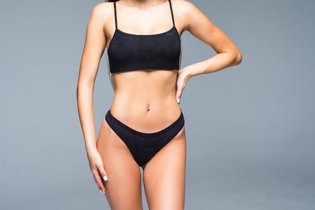 Alegre mulher sexy ajuste positivo em lingerie, apontando para sua barriga magro. mulher mostrando seu estômago liso, cintura ideal, mulher ostentando sobre seu peso. parede branca isolada, fitness, esporte Foto gratuita