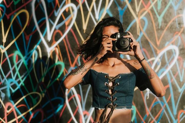Alegre mulher usando uma câmera instantânea Foto gratuita