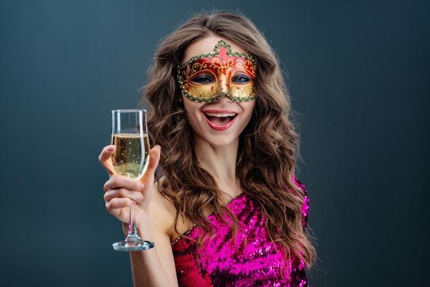 Alegre mulher vestindo máscara de carnaval veneziano sorri amplamente contra o fundo azul Foto Premium
