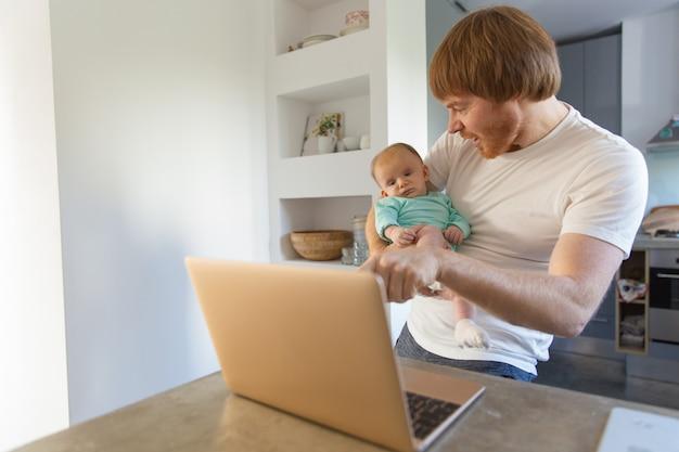 Alegre novo pai e sua filha bebê assistindo conteúdo Foto gratuita