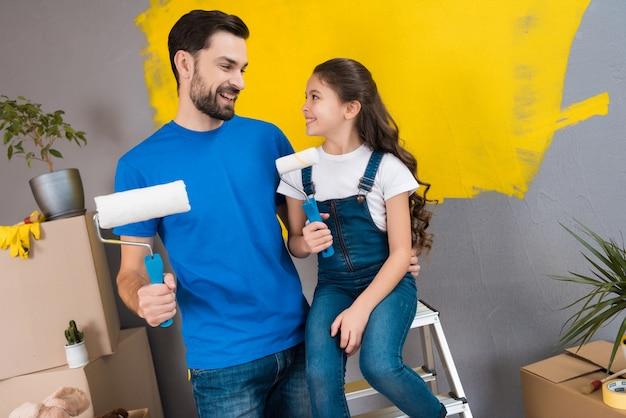 Alegre pai barbudo e pequena filha plano para pintar a parede Foto Premium