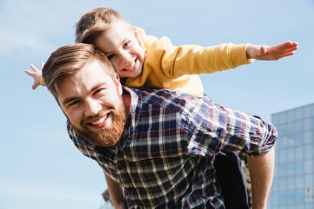 Alegre pai barbudo se divertindo com seu filho pequeno Foto gratuita