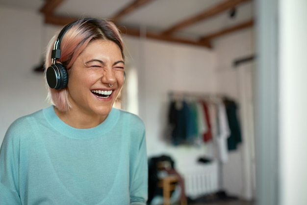 Alegre positiva jovem blogueira com argola no nariz, rindo durante a gravação de podcast, usando fone de ouvido. Foto gratuita