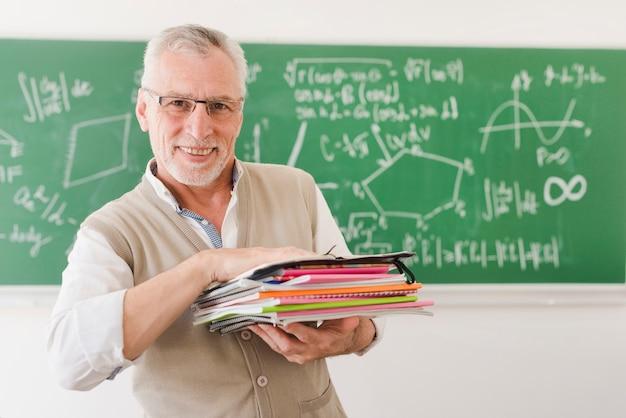 Alegre, professor sênior, segurando, pilha, de, cadernos, em, sala lecture Foto gratuita