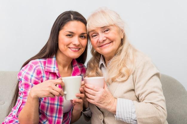 Alegre retrato de mãe e filha adulta segurando a caneca de café na ...