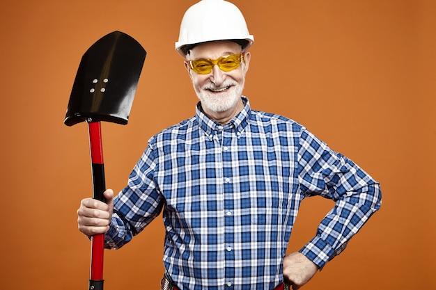 Alegre trabalhador da construção civil na aposentadoria usando capacete protetor e óculos amarelos, usando uma pá para cavar, posando isolado contra a parede em branco do copyspace Foto gratuita