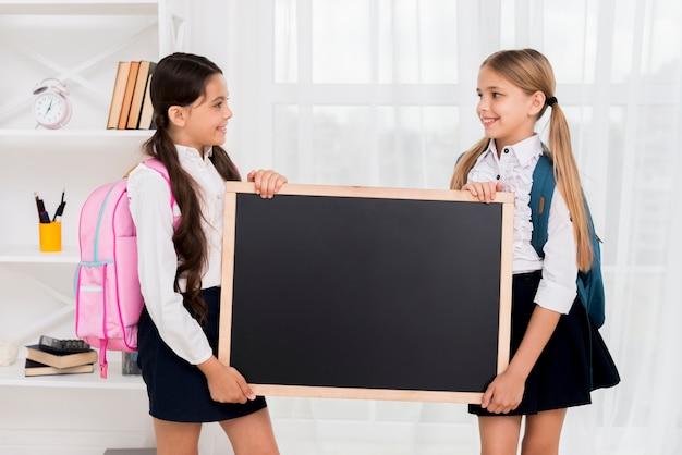 Alegres alunas com mochilas segurando o quadro-negro no quarto Foto gratuita