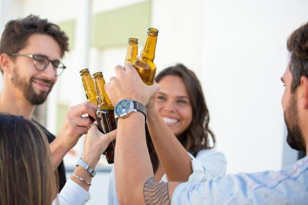 Alegres amigos brindando cerveja e comemorando o sucesso Foto gratuita