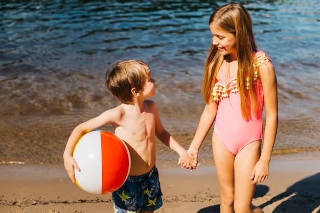 Alegres crianças olhando uns aos outros na costa Foto gratuita