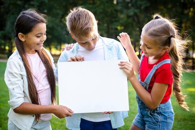 Alegres crianças segurando um papel em branco Foto gratuita