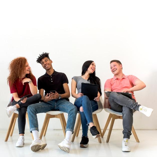 Alegres, multiétnico, amigos, segurando, dispositivo eletrônico, sentando, em, sala aula Foto gratuita
