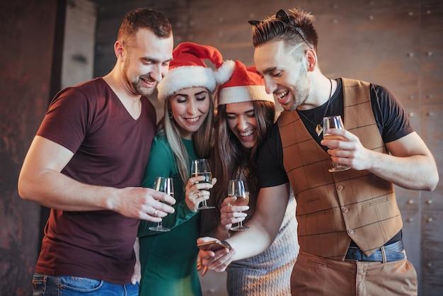 Alegres velhos amigos se comunicam e relógio do telefone, com taças de champanhe na festa de ano novo. conceito de entretenimento e estilo de vida. wifi pessoas conectadas Foto Premium