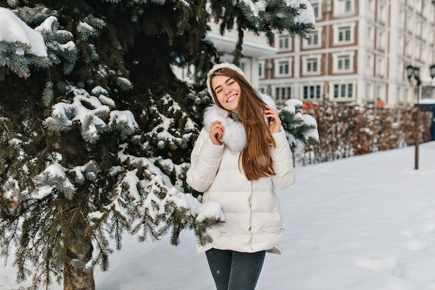 Alegria, felicidade da incrível garota linda sorrindo com roupas quentes de inverno na árvore sexta-feira cheia de espaço de neve. Foto gratuita