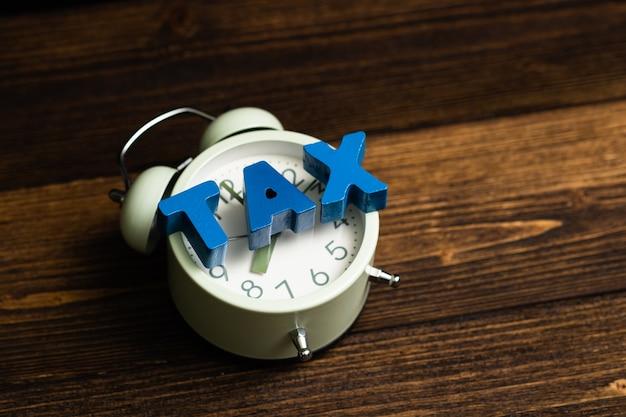 Alfabeto de imposto e despertador vintage na madeira Foto Premium